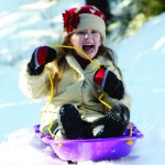 Young girl sledding in the snow