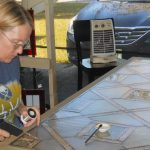 Carolyn Adamczyk creating a stained glass panel